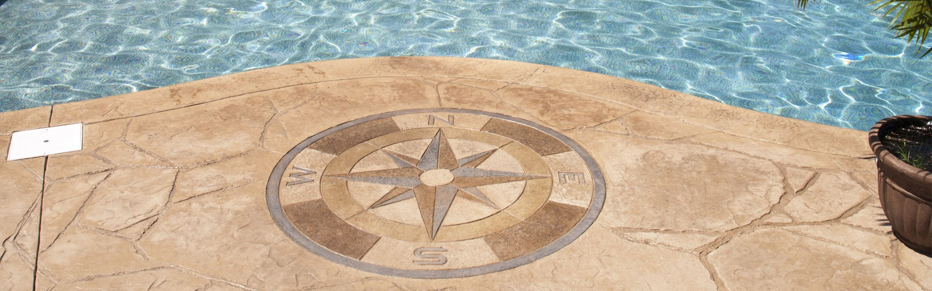 Compass made out of concrete near a pool.